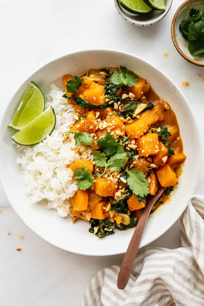 butternut squash curry and rice in a white bowl with a napkin on the side