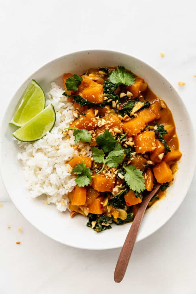 A bowl of butternut squash curry topped with cilantro and a lime wedge
