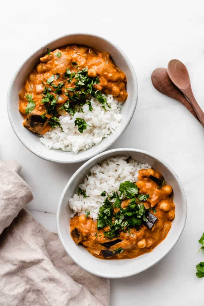 two bowls of eggplant curry and rice topped with chopped cilantro