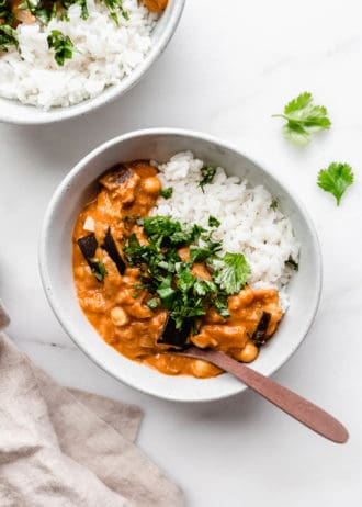 A bowl of eggplant curry with rice topped with cilantro