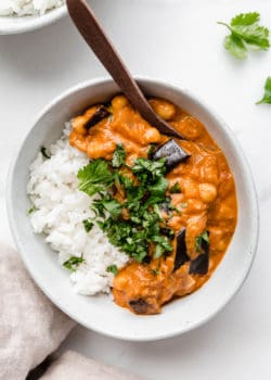 Eggplant curry and rice in a white bowl with a wood spoon