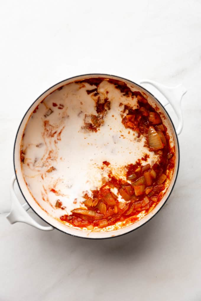 A white pot with coconut milk and tomato sauce in it