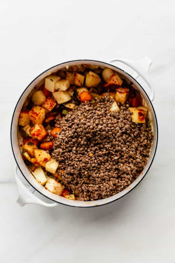 A white pot with brown lentils and potatoes in it