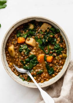 lentil stew in a bowl with a brown napkin on the side