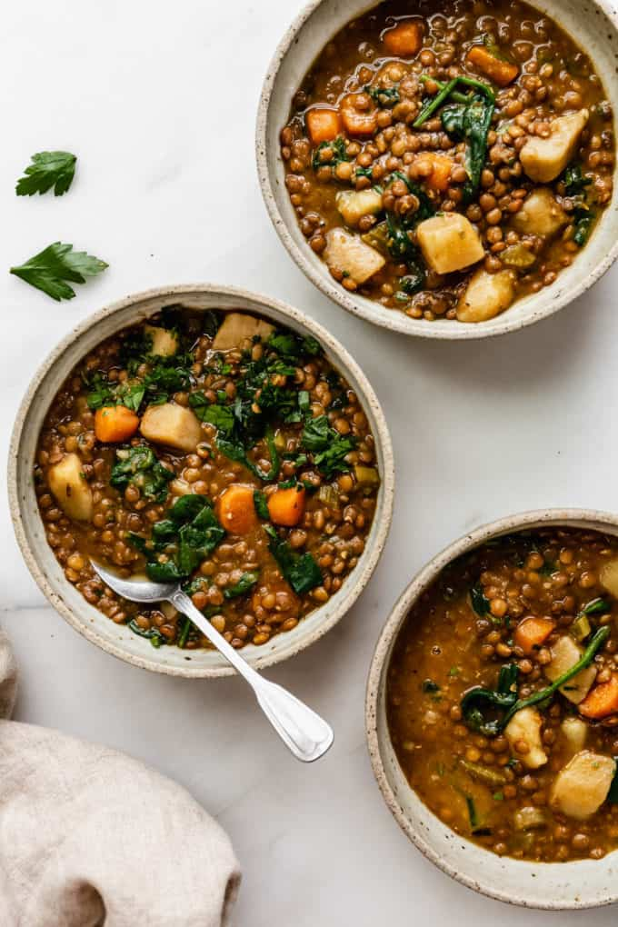 three bowls of lentil stew with parsley on top