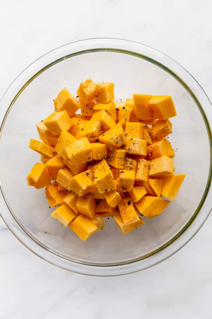 A clear mixing bowl with cubes of pumpkin it it tossed in olive oil, salt and pepper