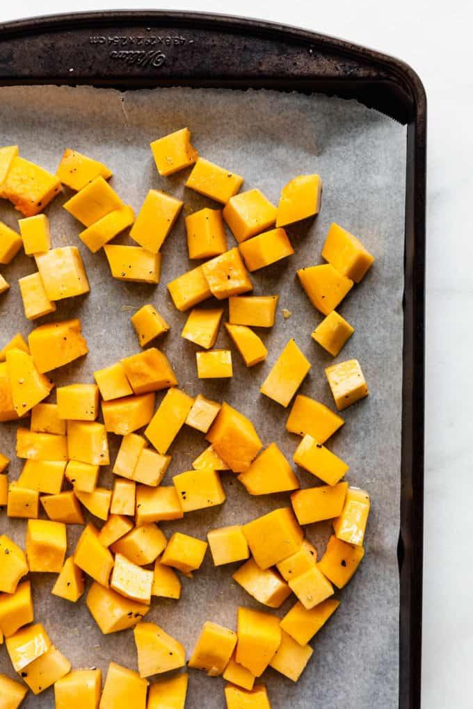 cubes of uncooked pumpkin on a baking sheet