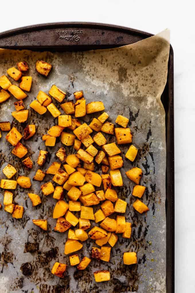 roasted pumpkin cut into cubes on a baking sheet