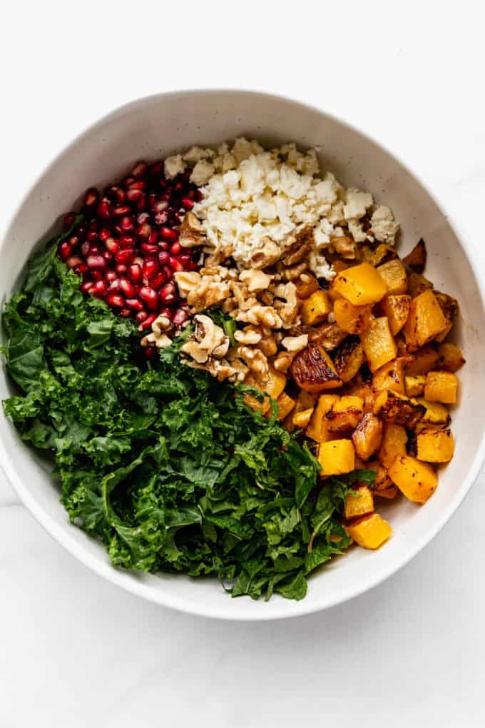 A white mixing bowl with kale, roasted pumpkin, walnuts, feta and pomegranate in it