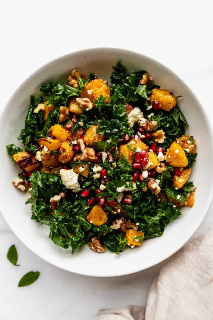 A white bowl with roasted pumpkin salad in it and a beige napkin on the side