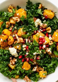A close up of a kale and pumpkin salad topped with walnuts and pomegranate