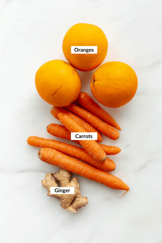 oranges, carrots and ginger on a marble board