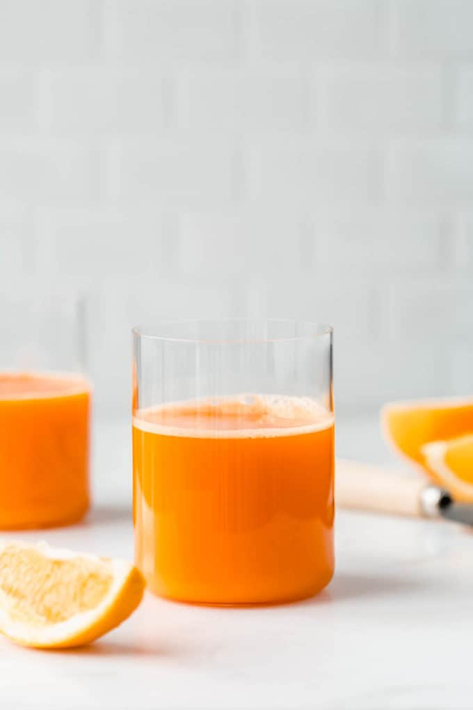 Two glasses or orange and carrot juice on a counter with sliced oranges around them
