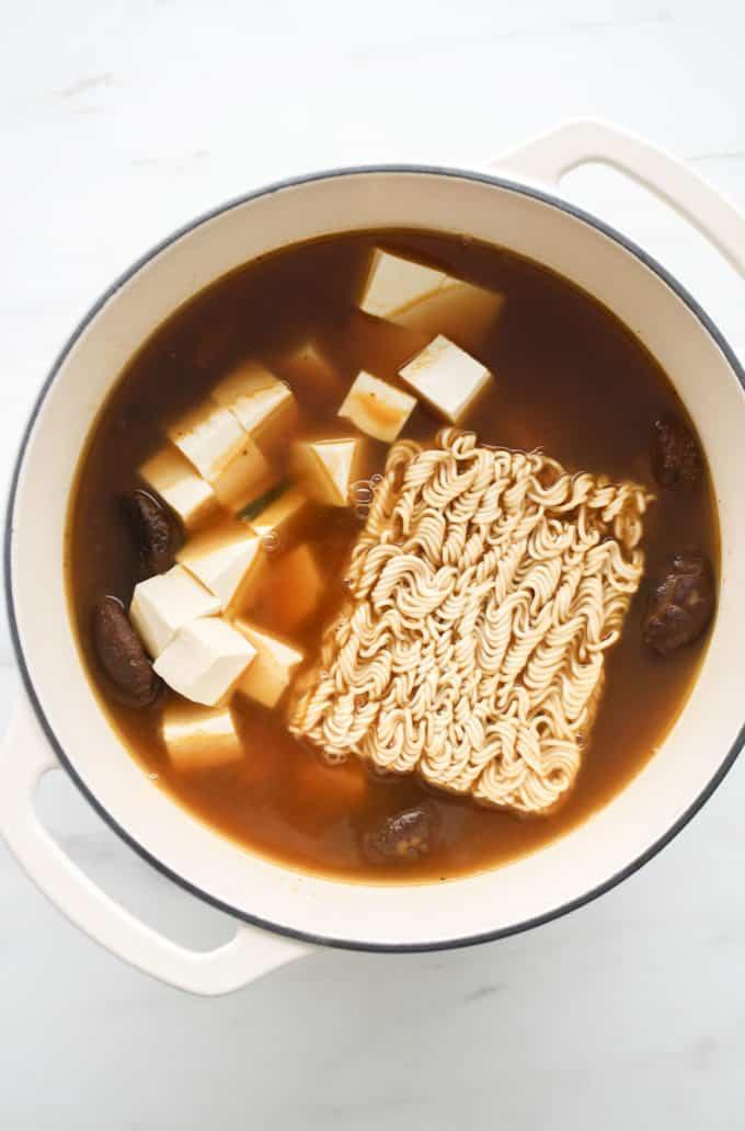 Vegan ramen soup with tofu and ramen noodles in a white pot