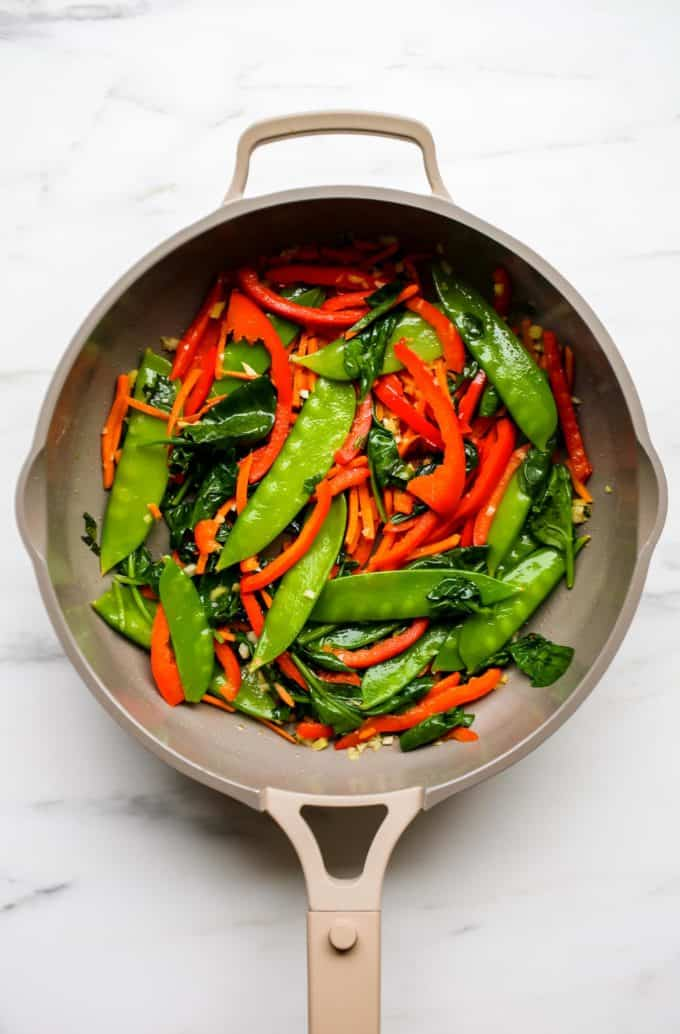 A pan with snow peas, peppers, carrots and spinach in it